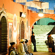 Locals sit on benches under the colorfully decorated arches of the town hall at night. In the background to the right are the white steps of Iglesia de Santo Tomas. Chichicastenango is an indigenous Maya town in the Guatemalan highlands about 90 miles northwest of Guatemala City and at an elevation of nearly 6,500 feet. It is most famous for its markets on Sundays and Thursdays.