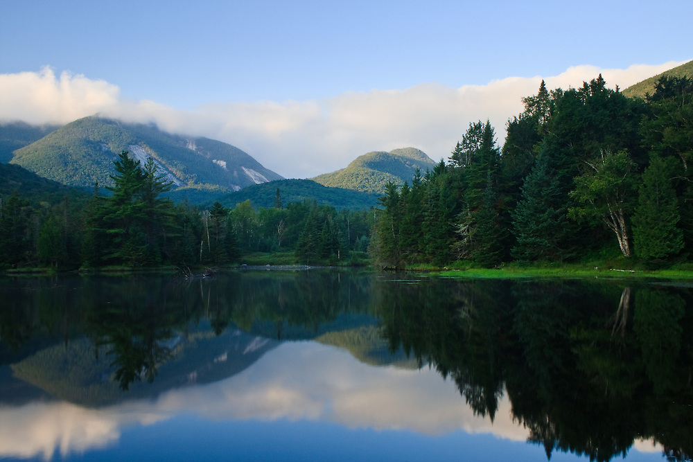 Mountains and clouds reflected in Marcy Dam Pond just after sunrise, Marcy Dam, High Peaks Wilderness, Adirondack State Park, New York. Visible in this image are Mount Colden and Avalanche Mountain and parts of both TR Mountain and Algonquin Peak.