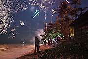 People enjoy fireworks and celebrate New Year on a beach in Batu Ferringhi on Penang, Malaysia.