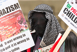 London, August 23rd, 2014. A faceless protester demands a boycott of Israeli goods as hundreds of pro- Palestine protesters demonstrate outside Downing Street demanding that Britain stops arming Israel.
