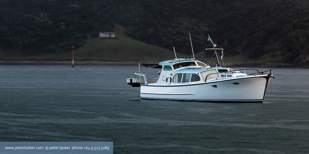 The launch Jolly Roger, anchored and fishing, early morning, in rain, off Matarahui Bay, Waiheke Island, Hauraki Gulf, Auckland, New Zealand.