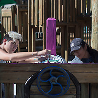 Anastacio Romero, left, and Candie Jurado from Deming paint the trim of a wooden train at the Field of Dreams Playground in Gallup Sunday as part of the Skills USA leadership conference.