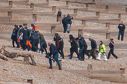 © Licensed to London News Pictures. 16/05/2020. Hastings, UK. Migrants are helped ashore at Pett Level near Hastings in East Sussex by the emergency services after crossing the English Channel earlier today in an inflatable boat. The group, possibly numbering up to 20 people including young children, were taken under tow by the Hastings Lifeboat and brought ashore by the Pett Level Independent Rescue Boat. They were met by coastguard and other government officials. Photo credit: Andrew Heather/LNP
