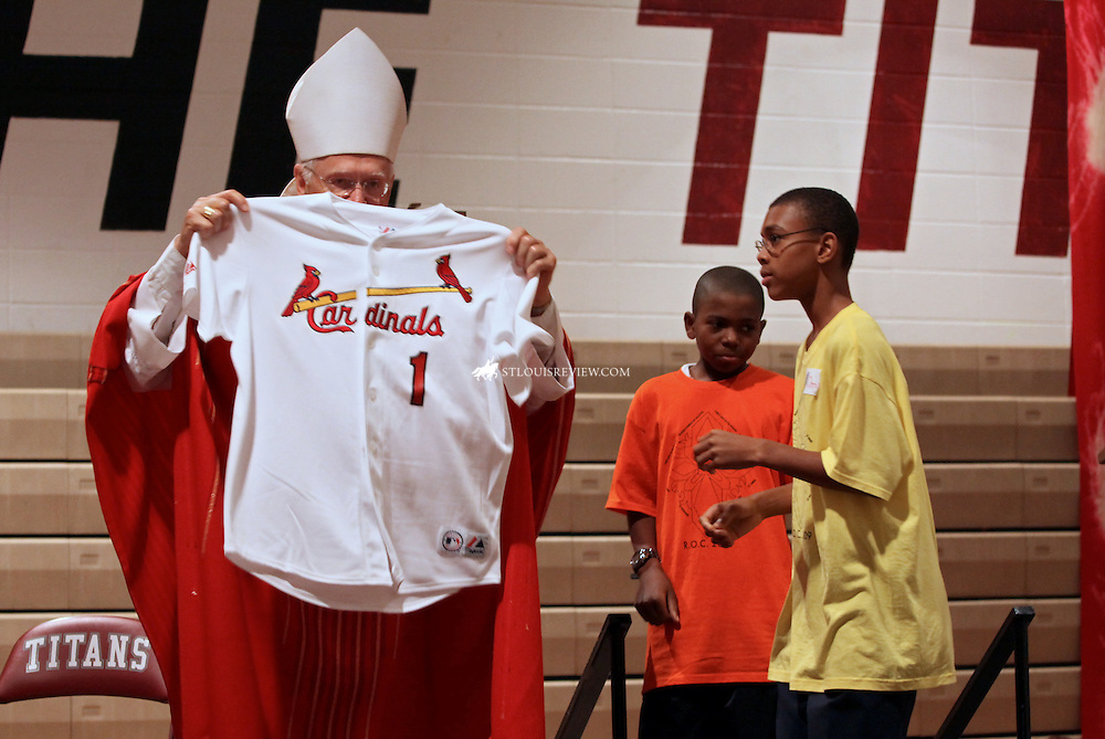 (9-18-09) Bioshop Robert Hermann held up the Cardinal shirt he was given at the Confirmation Rally for the North Side Deanery at Trinity High School.  The gift was presented after Communion during the Mass that was celebrated for several hundred young people preparing for Confirmation.  The back of the shirt says Hermann 1.