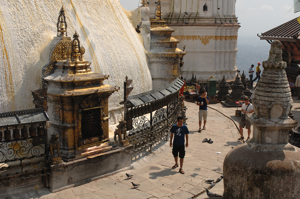 A person walking around the Swayambhunath stupa - the Monkey Temple - in Nepal, with prayer wheels along the circumference.
