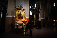 A woman lights candles inside the Orthodox Church of the Holy Spirit in Vilnius, Lithuania