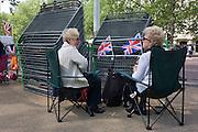 24 hours before the royal marriage of Prince William and Kate Middleton, royalists sit by stacks of railings that are to be used soon to fence off the masses from the passing procession. Taking place on Friday 30th April in front of millions of Britons and foreign tourists (many American), the crowds are already gathering to claim their ideal locations in the front rows along the procession route.
