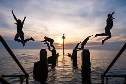 ©Licenced to London News Pictures<br /> 25 June 2018 . Aberystwyth Wales UK<br /> UK Weather:  A group of young people  in silhouette jumping into the sea together off the jetty on Aberystwyth beach at dusk at the end of another glorious day of hot unbroken sunshine.<br /> The UK is heading  into a mini heatwave, with temperatures forecast to hit 29º or 30º Celsius by the middle of the week<br /> <br /> photo credidKeith Morris / LNP