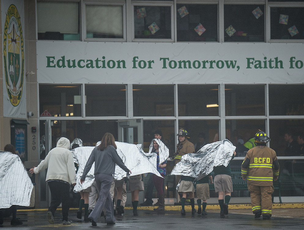 Students return after fire companies investigate the smoke condition and power outage at Saint Paul's School in Burlington, N.J., Monday, January 12, 2015.  Students had been evacuation to the Burlington City High School for an hours as officials investigated.   Photo by Bryan Woolston / @woolstonphoto.