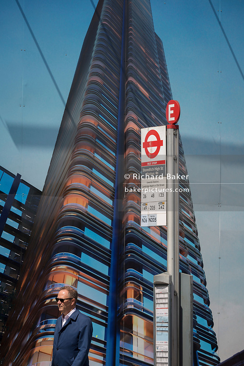 A man walks beneath a construction hoarding showing the Foster-designed Principal Tower that's under construction on Shoreditch High Street, on 10th May 2017, in London, England.