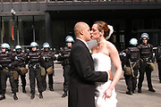 A newly married couple kisses in front of riot police at the Federal Plaza in Chicago during an anti-war protest.