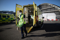 © Licensed to London News Pictures . 21/04/2020. Manchester, UK. Deep cleaning specialists clean an ambulance used to carry a Coronavirus patient to the Nightingale Hospital . The National Health Service has built a 648 bed field hospital for the treatment of Covid-19 patients , at the historical railway station terminus which now forms the main hall of the Manchester Central Convention Centre . The facility is treating patients from across the North West of England , providing them with general medical care and oxygen therapy after discharge from Intensive Care Units . Photo credit : Joel Goodman/LNP