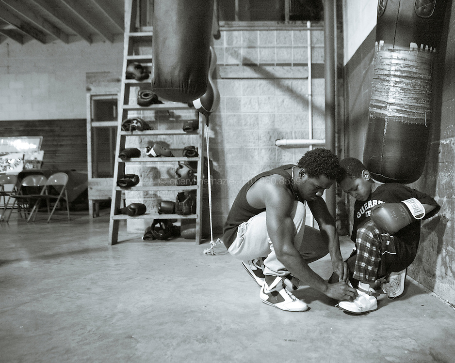 Fernando Guerrero takes a break to adjust a young boxer's shoe.