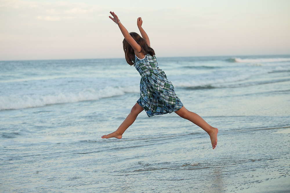 Photograph of a Young girl leaping in the air as waves break on Nauset Beach
