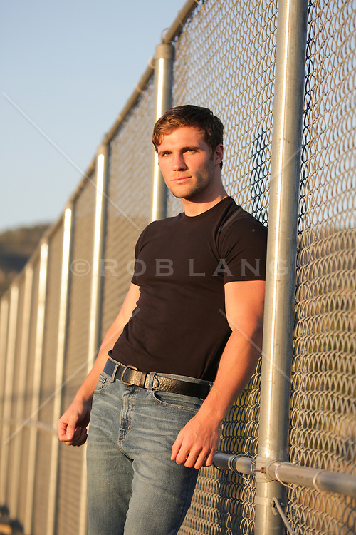 rugged good looking man in a black tee shirt by a chain link fence at sunset