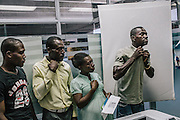 A man fixes his shirt before getting photographed and fingerprinted as part of the registration process.