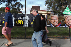 © Licensed to London News Pictures. 7/9/2013. Australian voters  walk past Labour, Liberal & Greens signage during the Australian Federal Election. Photo credit : Asanka Brendon Ratnayake/LNP