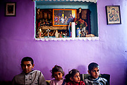 """Children and a member of the local Gospel band rehearsing inside a house at the Roma part at the district """"Podsadek"""". The town of Stara Lubovna has a population of 16350, of whom 2 060 (13%) are of Roma origin. The majority of Roma live in the Podsadek district, where 980 (74%) out of 1330 inhabitants are Roma."""