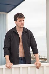 man in an open shirt on a beach balcony