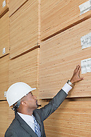 African American male engineer inspecting wooden planks