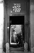 """BEIJING, CHINA - SEPTEMBER 2003 - A woman in a traditional Chinese home, which the character """"Fu"""" or happiness written above the main door, which is slated to be demolished in a """"hutong"""" or lane in the Chongwenmen area of central Beijing. Hutongs, maze-like gray-walled residential areas that have defined Beijing since the beginning of the Yuan Dynasty nearly 800 years ago are being systematically destroyed in an effort to spruce up Beijing before the Olympics in 2008. The Beijing government has defended its unpopular urban renewal scheme that had moved tens of thousands of families out of traditional neighborhoods in the city center, and said that plans to move ahead with further destruction of old historic areas was temporarily on hold. According to state media reports, about a third of the 62 square km old city has been demolished to make way for broader streets and modern buildings. A sizeable portion of this renovation had occurred since China won the bid to host the 2008 Olympics. The number of hutongs has fallen from more than 36,000 in the 1980's to just over 2000."""