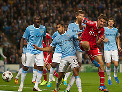 02.10.2013 Manchester, England.  Bayern Munich's Thomas Muller beats Manchester City's Gael Clichy to the ball but the effort goes wide during the Group D UEFA Champions League game between, Manchester City and Bayern Munich from the Etihad Stadium.