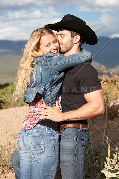 rugged cowboy with a beautiful blonde woman outdoors