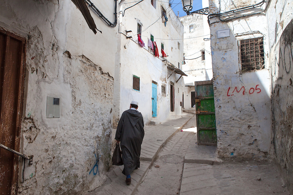 Arab muslim man, wearing a traditional djellaba, walking in the ancient whitewashed medina of Tetouan, northern Morocco, at the foot of the Rif Mountains.