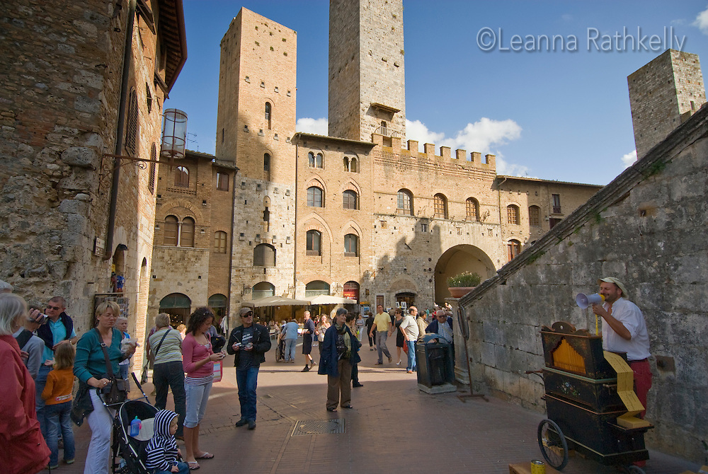 A musician sings with a player piano in the central piazza of San Gimignano, Tuscany, Italy.