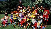Gruppenaufnahme von fröhlichen Kindergartenkindern mit Dreirädern, Hiva Oa, Französisch Polynesien * Group photo of happy kindergarden children with three-wheelers, Hiva Oa, French Polynesia