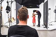 Young female child on a set during a photoshoot for a fashion company The stylist is adjusting the clothes and hair