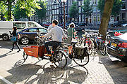 In Amsterdam rijdt een man op een bakfiets met een fiets aan zijn hand.<br /> <br /> In Amsterdam a man on a cargobike is transporting another bicycle on his hand.