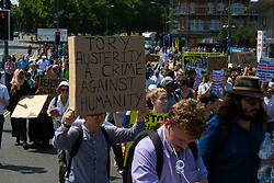 London, June 21st 2017. Protesters march through London from Sheherd's Bush Green in what the organisers call 'A Day Of Rage' in the wake of the Grenfell Tower fire disaster. The march is organised by the Movement for Justice By Any Means Necessary and coincides with the Queen's Speech at Parliament, the destination. PICTURED: Many placards lay the blame for the Grenfell Tower fire at the feet of the Tories and there austerity measures.