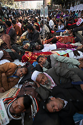 January 3, 2018 - Dhaka, Bangladesh - Non-MPO (monthly pay order) teachers from different non-government institutions, lay down in the street as they continue the four day of their fast unto death hunger strike program in front of the National Press Club in Dhaka, Bangladesh. Some hundred teachers went for hunger strike demanding their inclusion of the government-approved educational MPO facilities while more than 80,000 teachers from 5,242 non-MPO institutions are working without any pay, according to the leaders. (Credit Image: © Monirul Alam/NurPhoto via ZUMA Press)