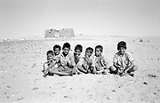 Group of 7 boys in desert with home in background