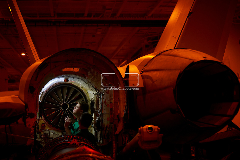 October 29, 2017. San Diego, California. Daily life on board the US Navy's Nimitz-class aircraft carrier, the USS Carl Vinson. The 1092 ft long, 95,000 ton vessel was training in the Pacific Ocean. Pictured is an F18 Super Hornet being repaired.<br /> Photo copyright John Chapple / www.JohnChapple.com