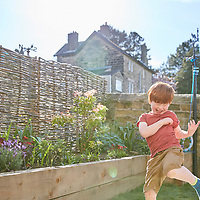 A photograph of a boy playing in the garden in the sunshine
