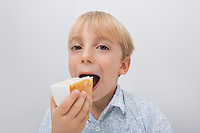 Portrait of cute boy eating cake slice against gray background