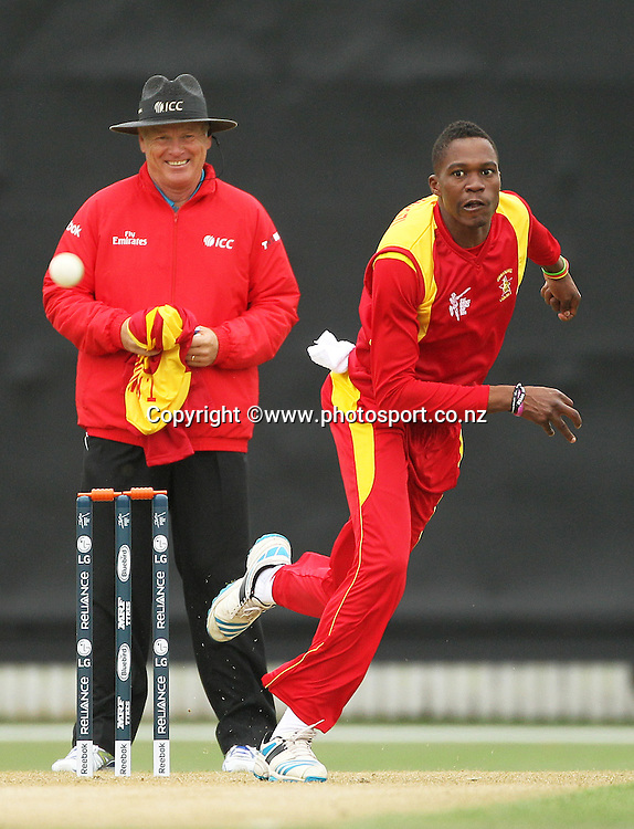 Tafadzwa Kamungozi of Zimbabwe is bowling and umpire Bruce Oxenford during the ICC Cricket World Cup warm up game between the Black Caps v Zimbabwe at Bert Sutcjliffe Oval, Lincoln, Christchurch. 9 February 2015 Photo: Joseph Johnson / www.photosport.co.nz