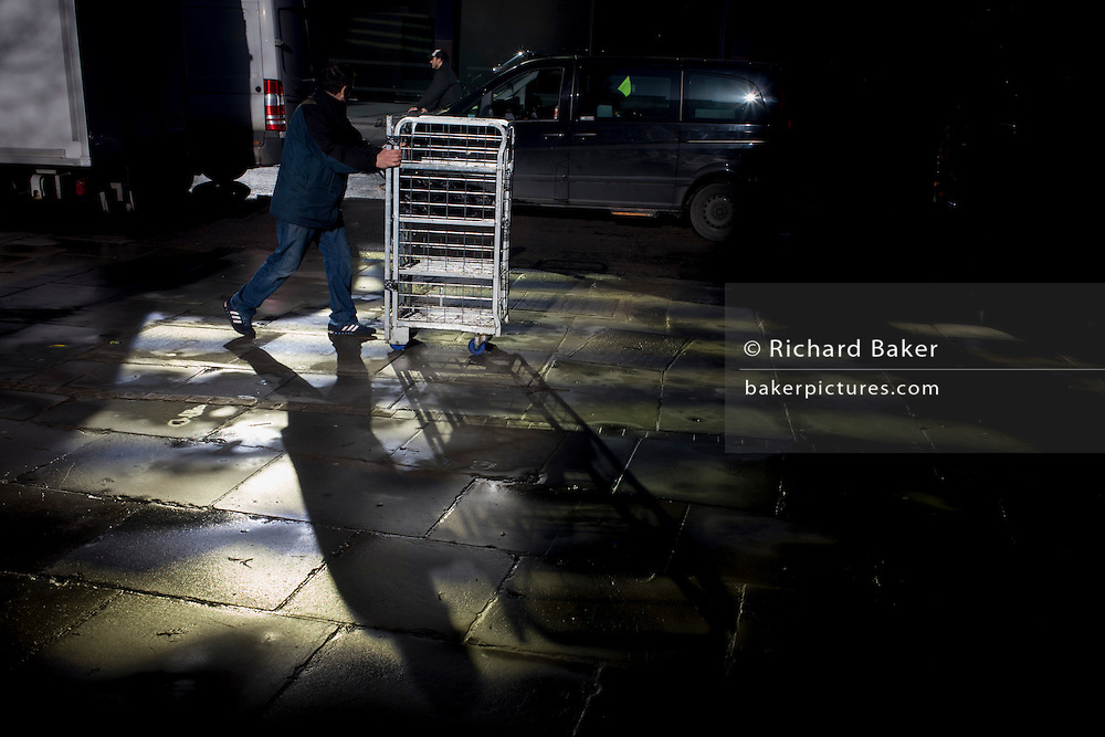 A delivery man pushes a goods cage and passes-by a pool of bright reflective light in the financial City of London.