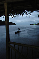 A fisherman in his dugout canoe returns home at dusk to his village on the Guatemalan-Belize border.