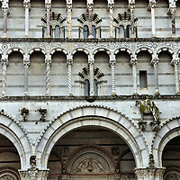 Duomo di San Martino Façade Detail in Lucca, Italy<br /> This detail of the Duomo di San Martino's white and green marble façade displays the cathedral's beauty.  If you look closely, you'll notice that every column is unique.  Legend has it that before it was built in the early 13th century, a contest was held to determine the column design to use over the western entrance.  Apparently, the judges liked every entry so they used them all.