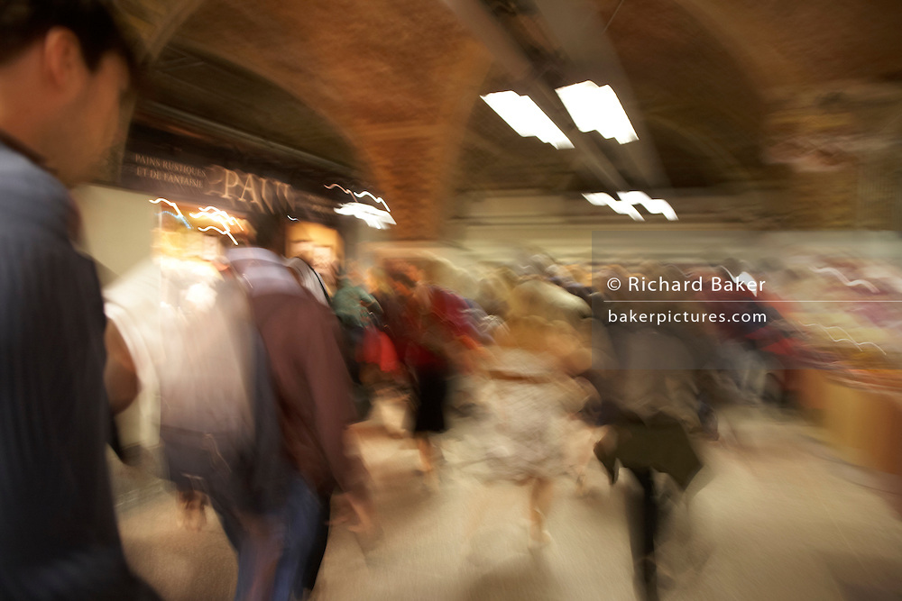 Rush hour train commuters blur through London Bridge mainline Station, walking en-route to exit and security barriers