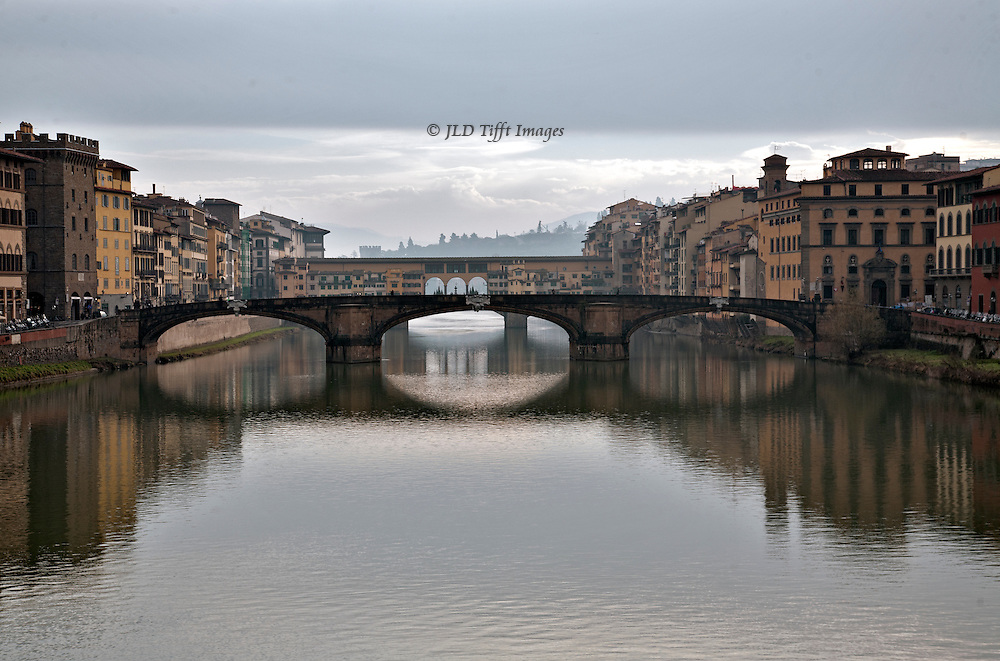Ponte Vecchio in soft colors on a cloudy day.  Subdued golds and pinks of the buildings along the river are reflected in the pale grey water.  The hill of San Miniato and a few bright clouds visible beyond the blanket of grey cloud above.