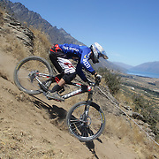 Dylan Sanchez-Pinsent from Dunedin in action during the New Zealand South Island Downhill Cup Mountain Bike series held on The Remarkables face with a stunning backdrop of the Wakatipu Basin. 150 riders took part in the two day event. Queenstown, Otago, New Zealand. 9th January 2012. Photo Tim Clayton