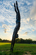"Old Westbury, New York, U.S., September 1, 2019. ""Athlete III - Deep Plunge"" is one of 33 outdoor sculptures by Jerzy Kedziora (Jotka), b. 1947 in Poland,, and his Balance in Nature art is on view at historic Old Westbury Gardens in Long Island, until October 20, 2019. Seen almost silhouetted by the sky at dusk, the life-size, bronze resin balancing sculpture, dressed in blue swimwear, appears about to dive into the lawn."