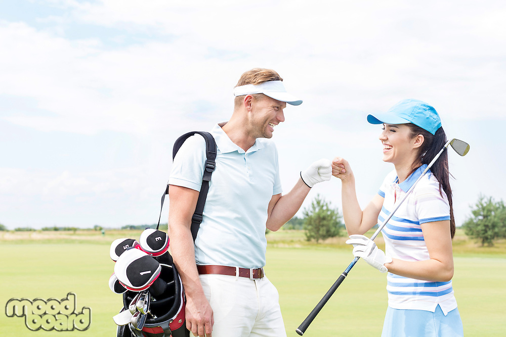 Cheerful friends giving high-five at golf course