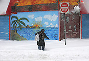 During a blizzard a woman struggles to walk in the snow in Harlem .