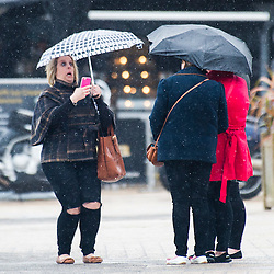 © Licensed to London News Pictures. 2/05/2016. CAberystwyth, Wales, UK.  A group of women, sheltering under umbrellas, taking photographs  in the rain on the deserted promenade on a dismal,  mild ,wet and grey  Bank Holiday Monday in Aberystwyth Wales. Photo credit: Keith Morris/LNP