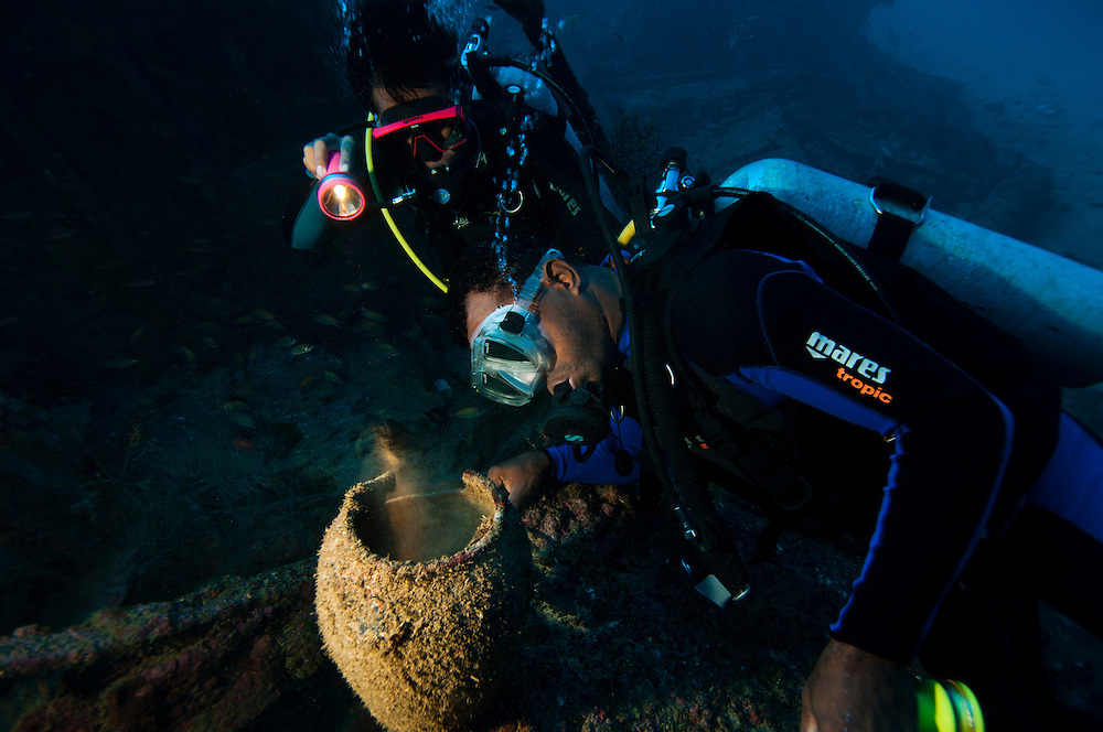 Divers examing pottery found on an unidentifed wreck, Manokwari, West Papua, Indonesia.